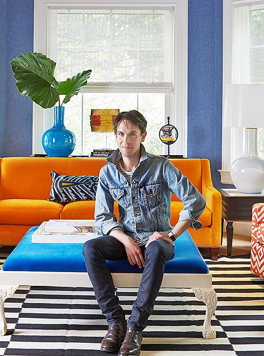 Interior designer Patrick Mele posing for a photograph in the apartment he decorated